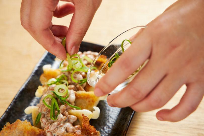 冷凍餃子の上に納豆、ネギとポン酢、ラー油をかける
