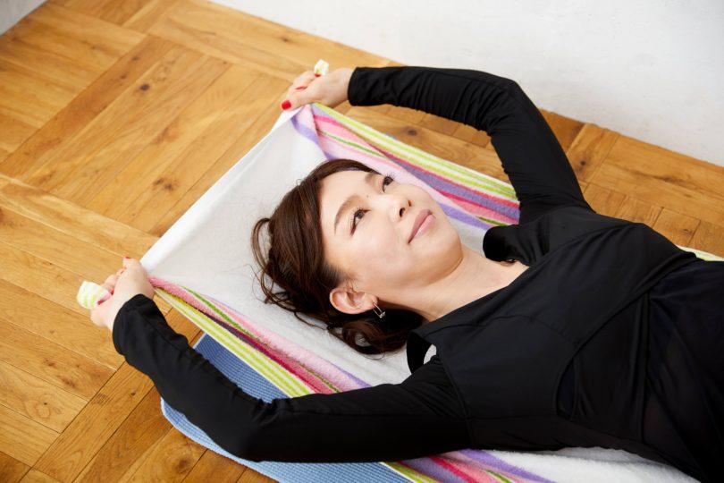 バスタオルの上に寝転んで、タオルの両端をしっかり握る