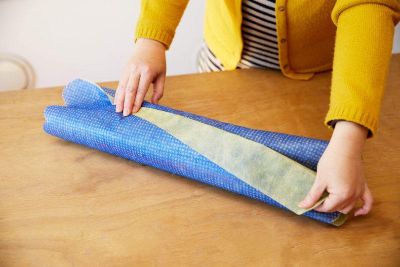 カットした辺をタテ向きに不織布を広げ、巻いたタオルをヨコ向きに置く。
