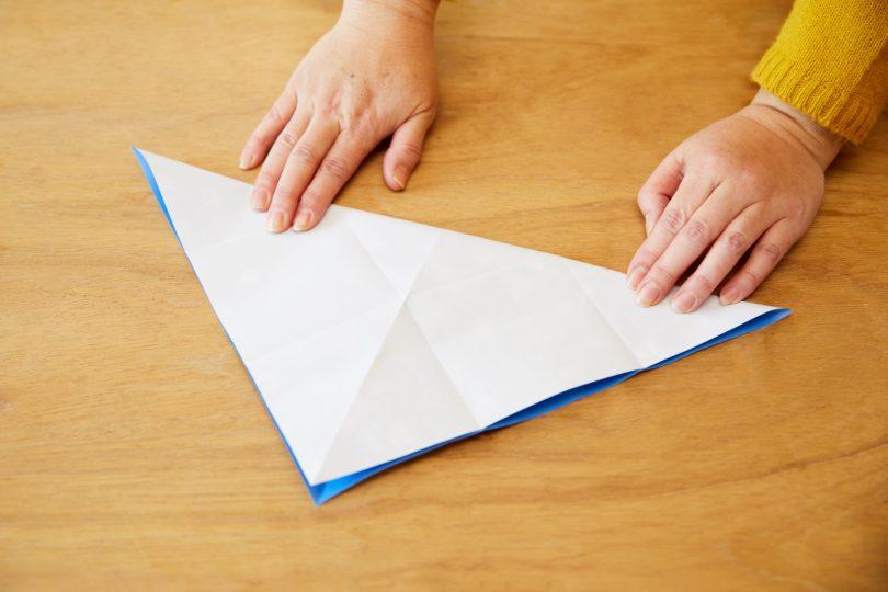 包装紙を開き、今度は柄のある面を表にして三角形に折る。