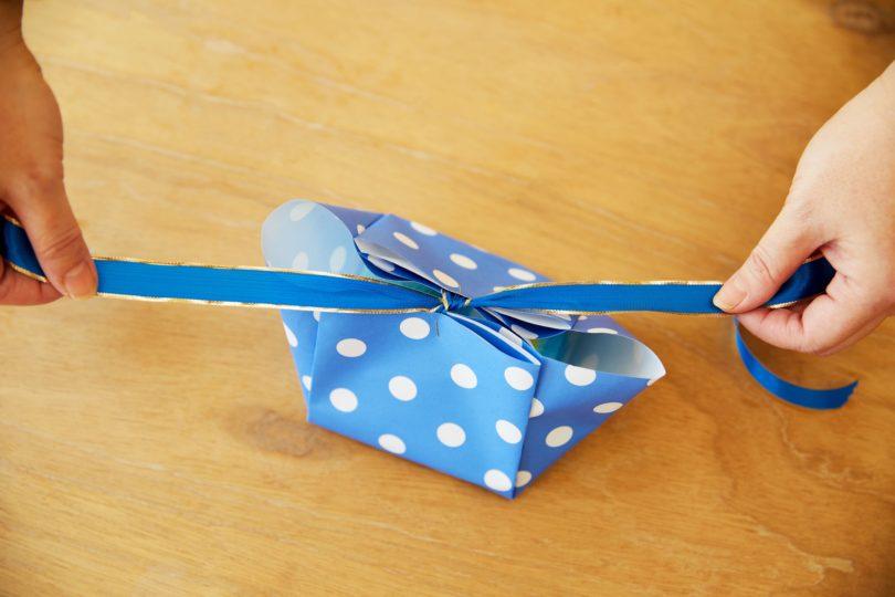 ステップ6の箱にタオルを詰め、留めたリボンを蝶結びし、ホチキスの針を隠すようにシールを貼る。