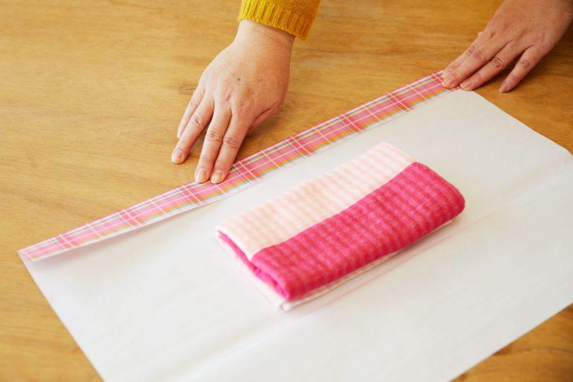 中央にタオルを置き、自分から見て包装紙の右側を3~5cmほど内側に折る。