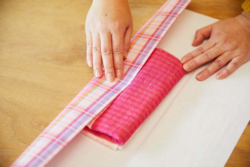 タオルの中心にステップ2の折り目が合わさるよう、包装紙を内側に折る。