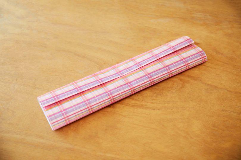 左側も内側に折ってタオルを包み、端を折り込んだ右側を上にしてセロハンテープで留める。